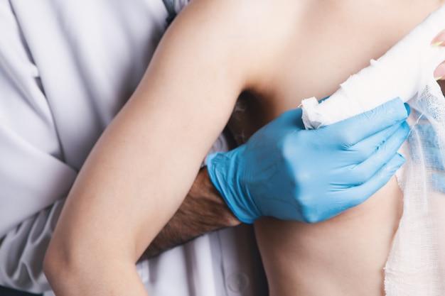 Lekarz owija bandaż wokół klatki piersiowej