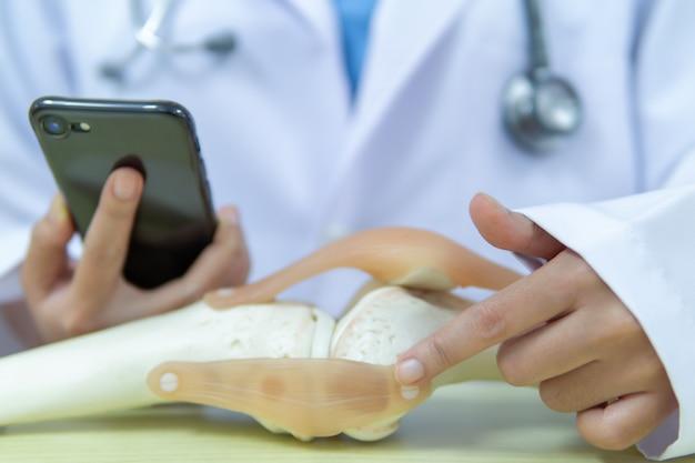 Lekarz patrzy na wizyty u pacjenta, który wymaga operacji wymiany stawu kolanowego