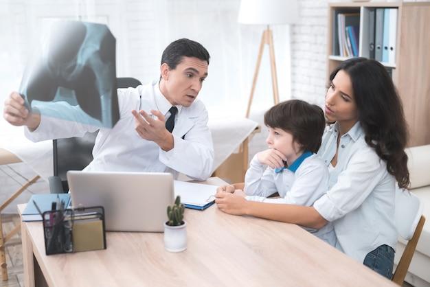 Lekarz patrzy na zdjęcie rentgenowskie dziecka.