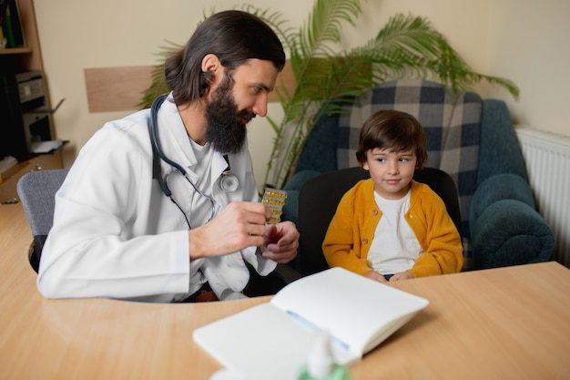 Lekarz pediatra badający dziecko w komfortowym gabinecie lekarskim. koncepcja opieki zdrowotnej, dzieciństwa, medycyny, ochrony i zapobiegania. mały chłopiec ufa lekarzowi i odczuwa spokojne, pozytywne emocje.