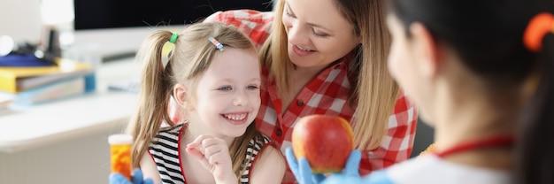 Lekarz pediatra oferujący matce i dziecku jabłko lub słoik leków