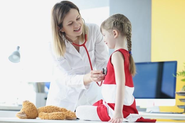 Lekarz pediatra słucha stetoskopem oddechu dziewczynki w gabinecie lekarskim