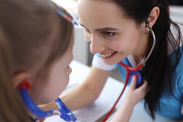 Lekarz pediatra słuchający serca małej dziewczynki stetoskopem w klinice