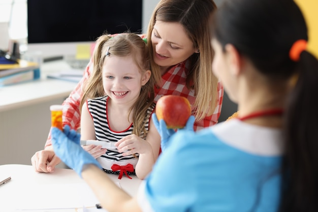 Lekarz pediatra trzymający butelkę z kapsułkami medycznymi i czerwonym jabłkiem przed małą dziewczynką i m...