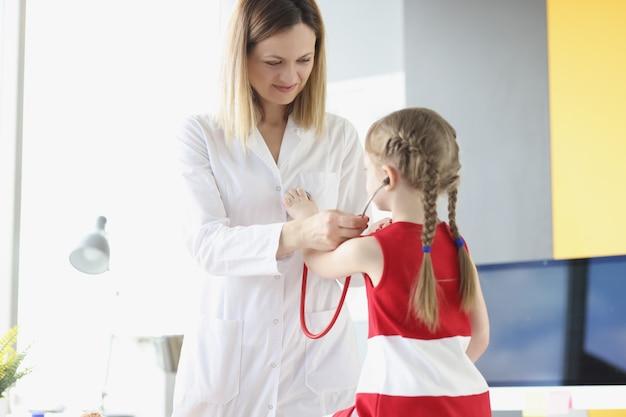 Lekarz pediatra wprowadzenie stetoskopu na dziewczynkę w koncepcji opieki nad dzieckiem w klinice