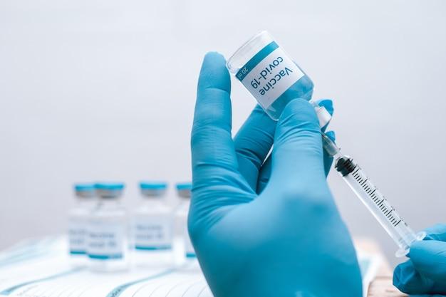 Lekarz, pielęgniarka, naukowiec ręka w niebieskich rękawiczkach trzymający grypę, odrę, koronawirus, chorobę szczepionkową covid-19 przygotowującą zastrzyk do szczepienia