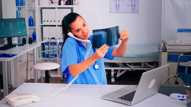 Lekarz pielęgniarka rozmawiająca przez telefon z pacjentem analizującym radiogram, omawiająca diagnozę, umawiająca się na wizytę. terapeuta, asystent lekarza pomagający w komunikacji telezdrowotnej, konsultacjach