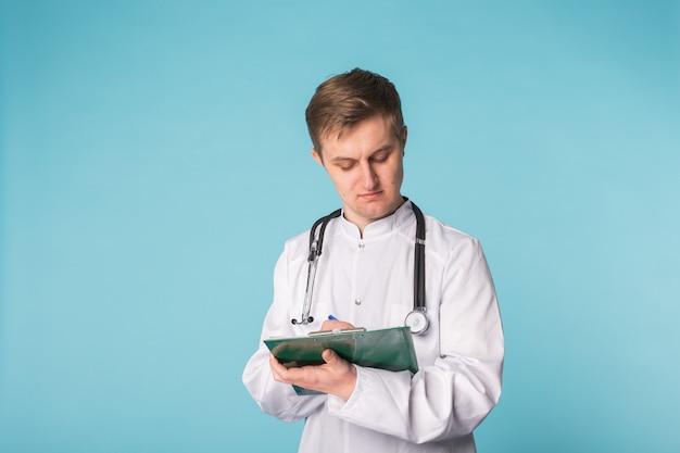 Lekarz pisze receptę na niebieskiej powierzchni z copyspace