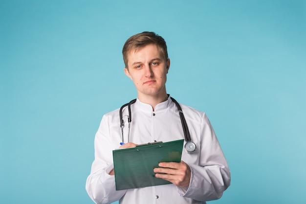 Lekarz pisze receptę na niebieskiej ścianie.