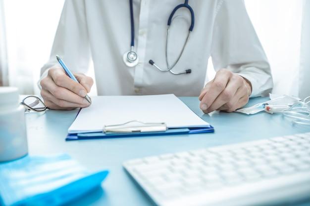 Lekarz pisze receptę na papier. raport medyczny.