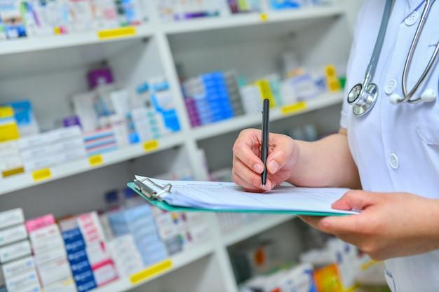 Lekarz pisze receptę z wieloma lekami na półkach