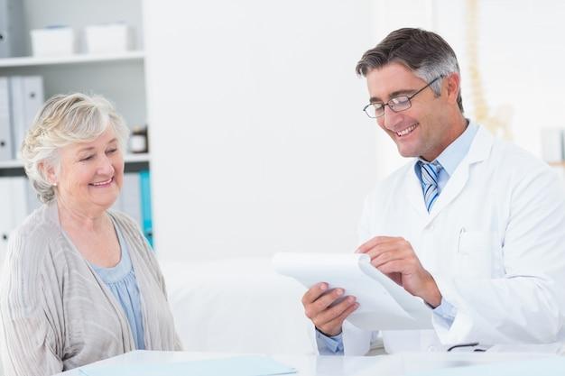 Lekarz pisze recepty dla starszych pacjentów