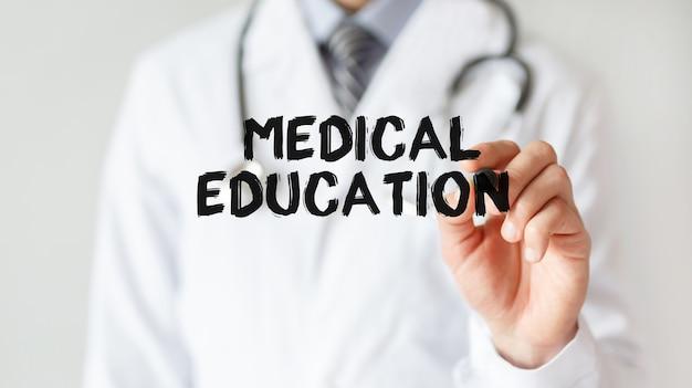 Lekarz pisze słowo edukacja medyczna z markerem, pojęcie medyczne