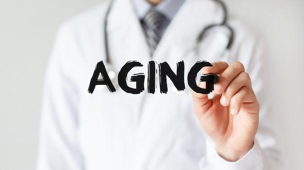 Lekarz pisze słowo starzenie się markerem, pojęcie medyczne