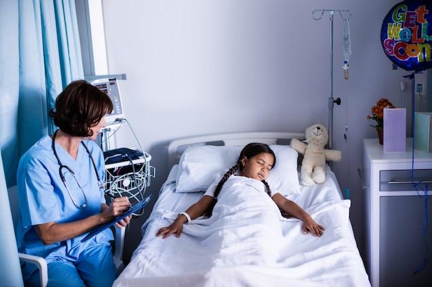 Lekarz pisze w schowku, patrząc na pacjenta