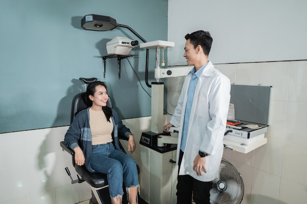 Lekarz płci męskiej i piękna pacjentka przebywają w gabinecie w poradni okulistycznej na badanie