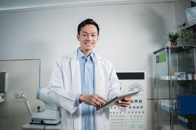Lekarz płci męskiej prowadzi okulistyczną listę kontrolną, która stanowi podstawę badań w poradni okulistycznej