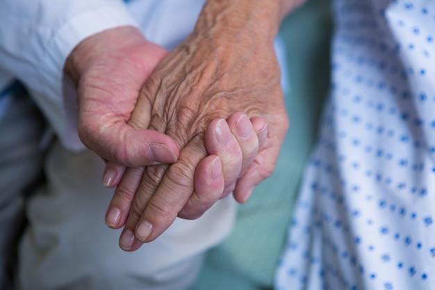 Lekarz pociesza starszego pacjenta w szpitalu