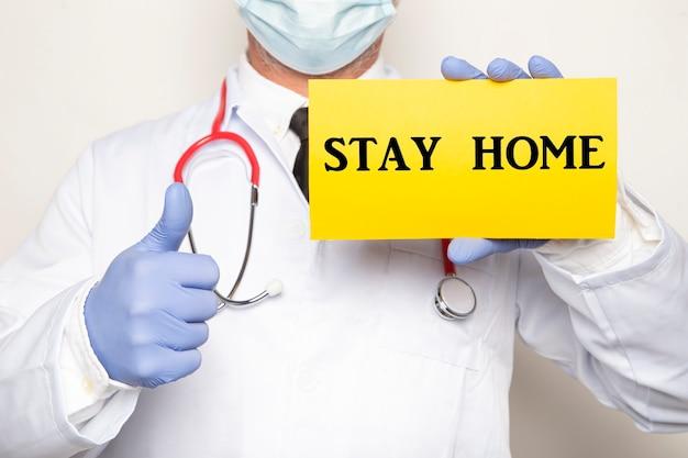 Lekarz podnoszący kciuk w zatwierdzeniu posiadania znaku z tekstem, pozostań w domu