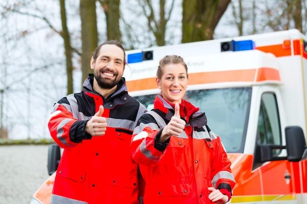 Lekarz pogotowia i pielęgniarka stoją przed karetką
