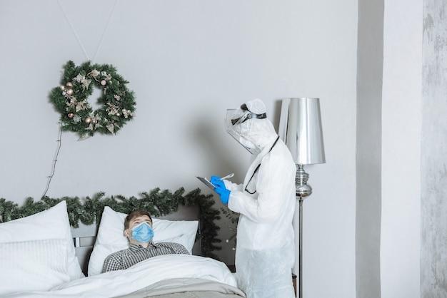 Lekarz pogotowia ratunkowego w kombinezonie ochronnym ppe hazmat bada chorego pacjenta z koronawirusem covid-19 przed nowym rokiem i bożym narodzeniem