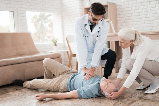 Lekarz pogotowia wykonuje resuscytację u starszego mężczyzny.