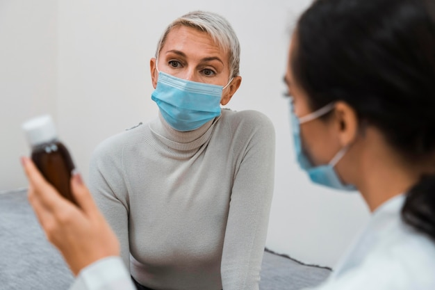 Lekarz pokazując pacjentowi butelkę leku