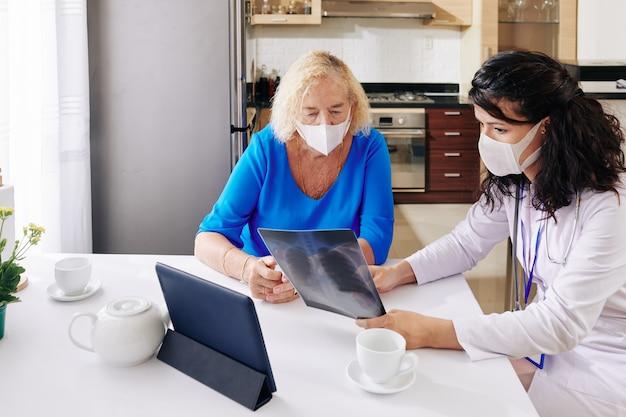 Lekarz pokazując prześwietlenie płuc pacjentowi