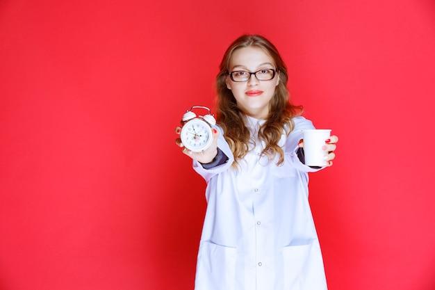 Lekarz pokazując zegar i kubek wody, co oznacza przyjmowanie leków na czas.