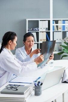 Lekarz pokazujący małą plamkę na prześwietleniu płuc niespokojnej starszej kobiety