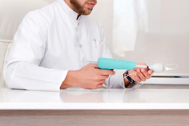 Lekarz pokazujący urządzenie do usuwania żylaków. flebolog mężczyzna chirurg pracuje w nowoczesnej klinice. narzędzia medyczne w szpitalu. leczenie żylaków.