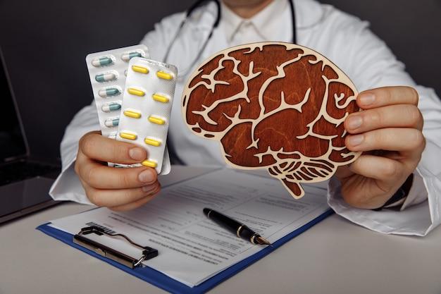 Lekarz pokazuje drewniany mózg i pigułki w swoim gabinecie.