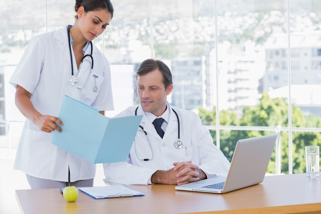Lekarz pokazuje folder do kolegi