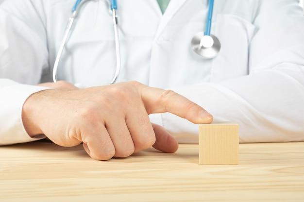 Lekarz pokazuje makiety puste drewniane kostki z pustym miejscem na tekst. lekarz zaleca przyjmowanie