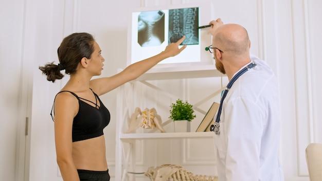 Lekarz pokazuje młodej kobiecie jej prześwietlenie oceniające stan pacjenta, aby zasugerować około...