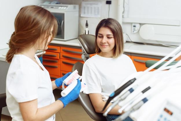 Lekarz pokazuje pacjentce, jak prawidłowo myć zęby elektryczną szczoteczką do zębów