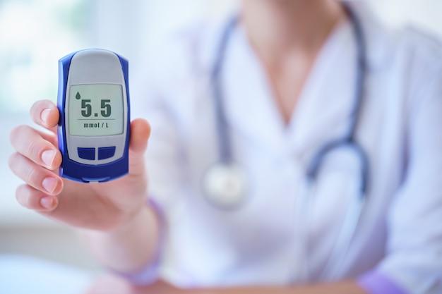 Lekarz pokazuje pacjentowi z cukrzycą glukometr z poziomem glukozy we krwi podczas konsultacji lekarskiej i badania w szpitalu. cukrzycowy styl życia i opieka zdrowotna