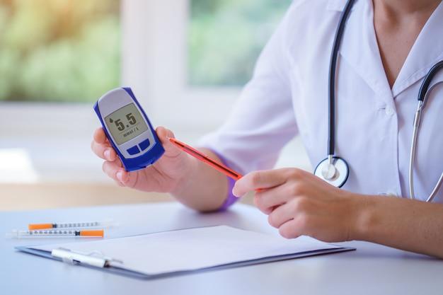 Lekarz pokazuje pacjentowi z cukrzycą glukometr z poziomem glukozy we krwi podczas konsultacji lekarskiej i badania w szpitalu. opieka zdrowotna
