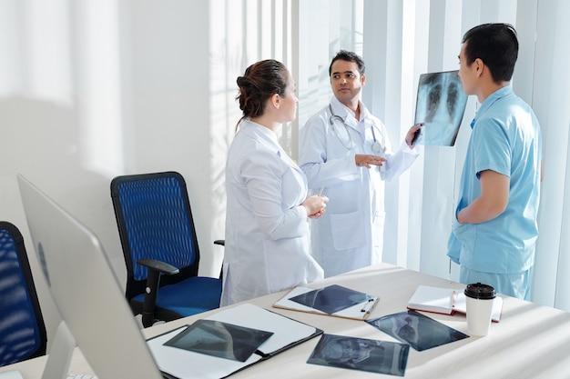 Lekarz pokazuje prześwietlenie klatki piersiowej