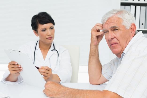 Lekarz pokazuje raporty zmartwiony starszy pacjent
