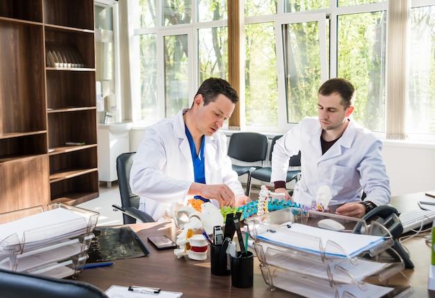 Lekarz pokazuje śrubę wieloosiową na modelu kręgosłupa.