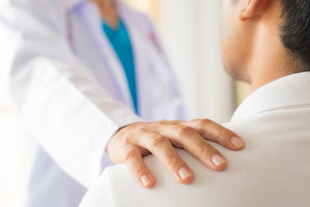 Lekarz położył rękę na ramieniu pacjenta, zachęcając i dyskutując