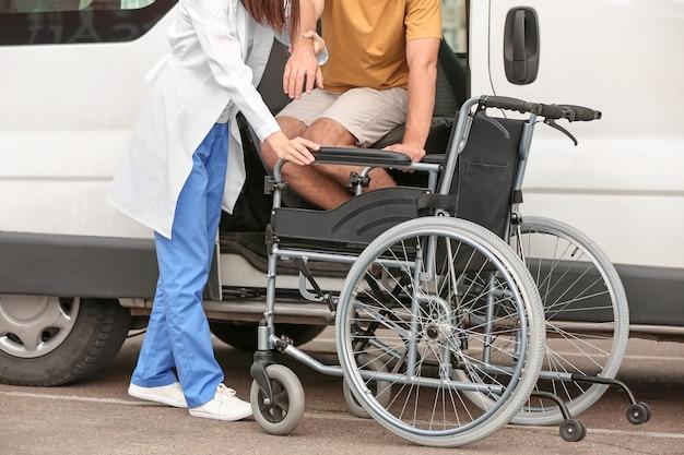 Lekarz pomaga niepełnosprawnemu człowiekowi usiąść w samochodzie