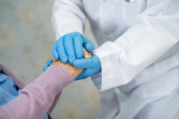 Lekarz pomaga pacjentce z azji w ochronie koronawirusa covid-19.