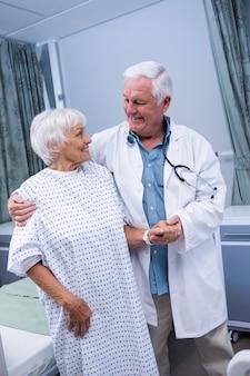 Lekarz pomaga starszemu pacjentowi w szpitalu