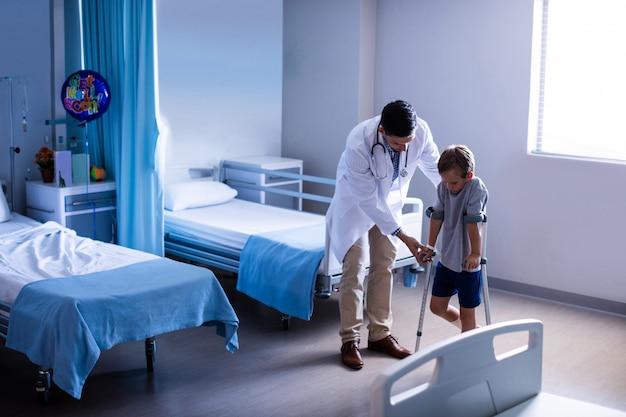 Lekarz pomagający poszkodowanemu chodzić o kulach