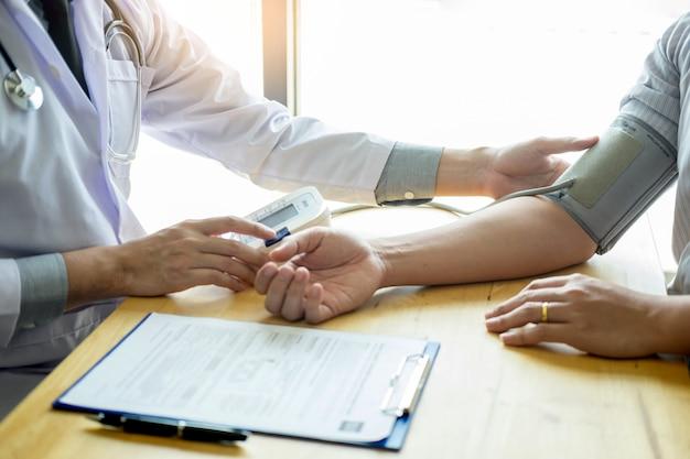 Lekarz pomiaru i kontroli ciśnienia krwi pacjenta w szpitalu, pojęcie opieki zdrowotnej.