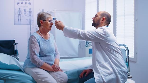 Lekarz pomiaru temperatury do starszej kobiety, która siedzi na szpitalnym łóżku. zastosowanie cyfrowego termometru bezkontaktowego na podczerwień w nowoczesnej prywatnej klinice. badanie lekarskie pod kątem infekcji i chorób
