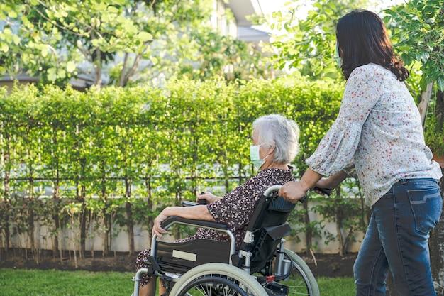 Lekarz pomoc i opieka azjatycka starsza kobieta pacjentka siedząca na wózku inwalidzkim w parku
