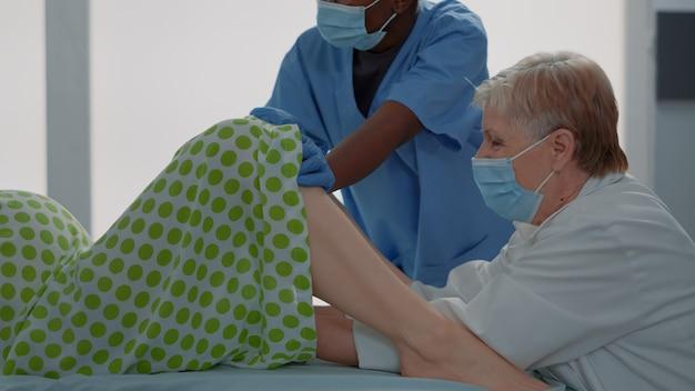 Lekarz porodowy pomaga kaukaskiej kobiecie dostarczać dziecko w łóżku na oddziale szpitalnym. afroamerykańska pielęgniarka asystująca położnikowi w klinice położniczej. wieloetniczny zespół medyczny